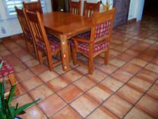 Why Are There Color Variations in Saltillo Tile? Saltillo tile usually varies in colour and shape, however the majority range from in varying hues of reds, oranges and yellows. These beautiful floor tiles are shaped by pressing quarried clay with a wooden frame (super), or could be carving out the desired shape (regular). Depending on the raw tile's placement among other tiles at the time of firing, its colour ranges from yellow to a rich orange. Since each piece of standard Saltillo tile is actually made individually by hand with no modern machinery involved, most pieces will have that individual character. The tile is primitive. There are irregularities. You will find small chips, cracks, and bumps. These imperfections merely add character and rustic quality to the floor. If you are lucky, you might even find a few animal footprints in your tile! With regard to color, lets talk about process a little since this accounts for the major changes you may see from one firing to the next. The tiles are stacked in the caves (kilns) on end which may slightly overlapp so they don't fall over. Then, before firing, the opening to the kiln is sealed with clay to prevent heat from escaping. The fire is started at the bottom of the cave and fuel is added to increase the heat until the proper temperature is reached. As you know, fire will not burn without oxygen, and at sometime during the firing process all of the available oxygen in the atmosphere in the cave is used up. At that point the flame then seeks the next available source of oxygen (which it finds in the form of iron oxide in the clay tile) and burns it, flashing the exposed surfaces of the tile. The light buff color in the tile is the area that was flashed; the peach color in the tile is the area, which is shielded from the flame by other tiles. You may hear many different stories about different types of fuel used in the firing of Saltillo tile. The original source of heat used for firing Saltillo tile was burning rubber tires. Most of the time, wood is now used to start the process. In the past few years, a variety of fuels have also been used, such as propane, diesel, crude petroleum, etc. The type of fuel used for firing does not directly affect the color of the tile. Heat is heat, much like a gas or electric stove. The color of the tiles may vary somewhat due to: Different ways the tile is stacked in the kiln. The way in which the flame/heat is controlled inside the kiln. Depending on if a color additive is added to the clay during the manufacturing process Whether a slight green hue is apparent from the firing process. Regardless of your choice of Mexican tile, be it Saltillo, Mission, Talavera or other varieties, you can't beat these tiling options for creating a traditional, southwestern atmosphere in any room of your house. Our job is to provide a professional installation and then keep them beautiful. Call us today for an estimate on installing, cleaning or restoring the Mexican Tile in your home or business. Keith Clay Floors is happy to assist you with any questions you may still have about Saltillo tile in general. Call us today, you will be so glad you did. World Class Craftsmanship. Reasonable Prices. Call Today: 972-463-6604
